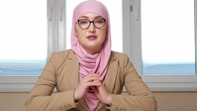 Woman in Hijab and Glasses Sits at the Table and Talks to the Camera Zooming Out of the Camera
