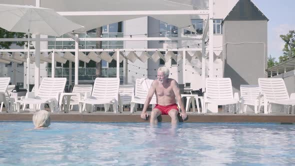 Thumbnail for Happy Mature Couple Relaxing at the Pool in the Hotel Complex Together
