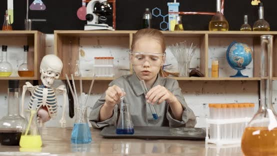 Laboratory Experience in a Chemistry Lesson, a Girl in Protective Glasses Pours a Blue Liquid Into a