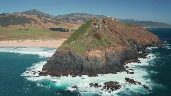Thumbnail for Cinematic Aerial View of a Lighthouse on a Scenic Green Rocky Island, Summer
