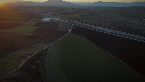 Thumbnail for Aerial view of a highway surrounded by agricultural fields at sunset.
