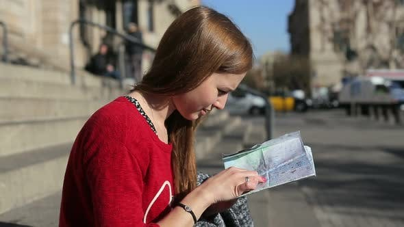 Thumbnail for Female on the Stairs Sees the Tourist Map Looking Around Traffic Behind