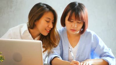 Two young business women sitting at table in cafe. Asian women using laptop and cup of coffee.