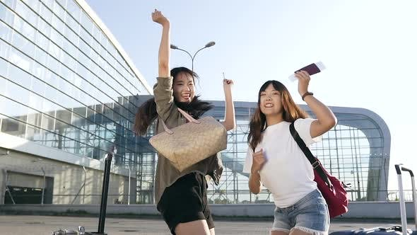 Thumbnail for Young Asian Brunettes Jumping from Joy with Air Tickets in Hands Before their Travel