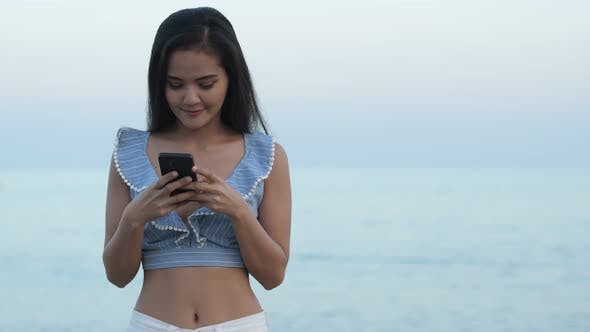 Thumbnail for Young Happy Asian Tourist Woman Using Phone By The Beach