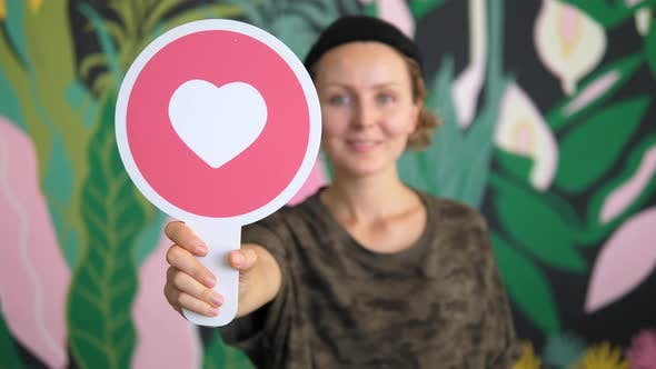 Thumbnail for Young Smiling Woman Voting With A Heart Symbol And Giving Like