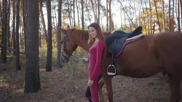 Thumbnail for Side View of a Young Caucasian Girl in Pink Clothes Walking with Beautiful Brown Horse Between Trees