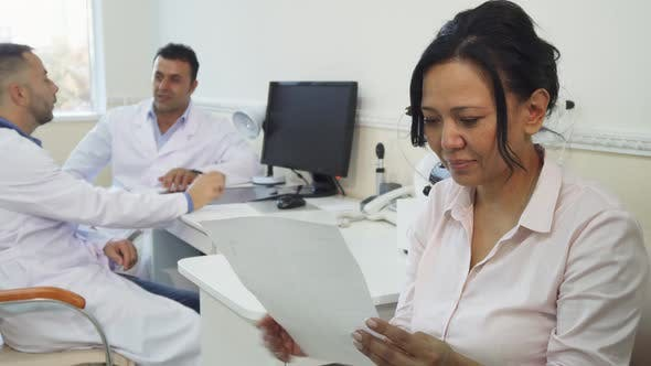 Thumbnail for A Satisfied Patient Studies Her Medical Certificate