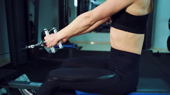 Thumbnail for Woman is Sitting Behind a Cardio Trainer and Working with Her Hands