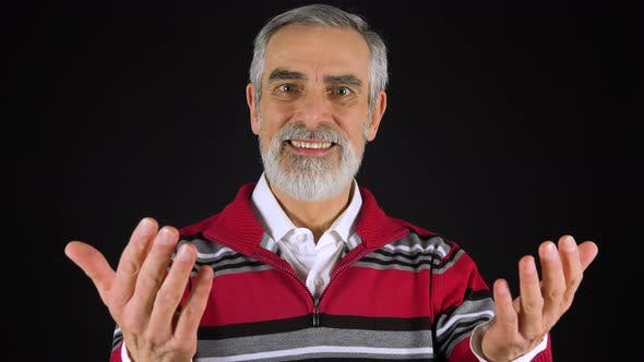 Thumbnail for An Elderly Man Smiles and Motions To the Camera in a Gesture of Invitation - Black Screen Studio