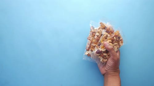 Hand Hold a Packet of Mixed Nuts on Blue Background