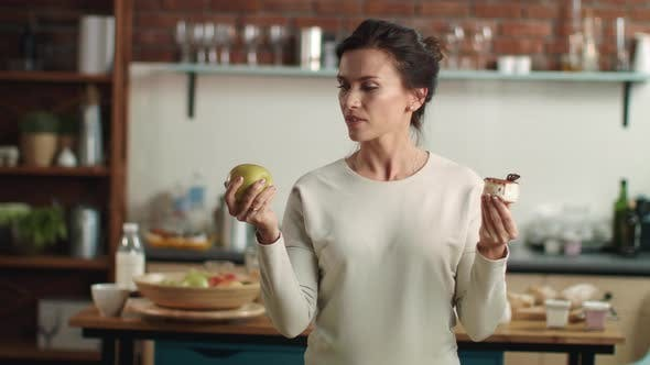 Thumbnail for Woman Making Choice Between Apple and Cake in Kitchen. Girl Choosing Fruit Diet.