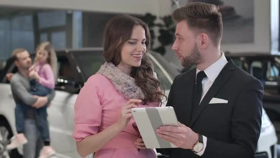 Thumbnail for Close-up of Beautiful Caucasian Woman Discussing Car Purchase with Trader. Successful Businesslady