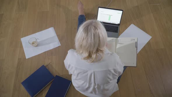 Cover Image for Top View of Caucasian Female Retiree in Casual Clothes Sitting on the Wooden Floor and Using Laptop