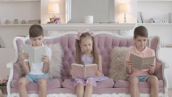 Thumbnail for Cute Brunette Girl Sitting on Couch with Twin Brothers and Reading Book, Portrait of Little
