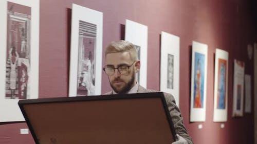 Männlicher Galeriearbeiter, der durch die Galerie mit Malerei geht