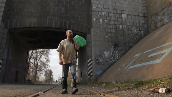 Thumbnail for Full Length Unemployed Man Walking Under Bridge