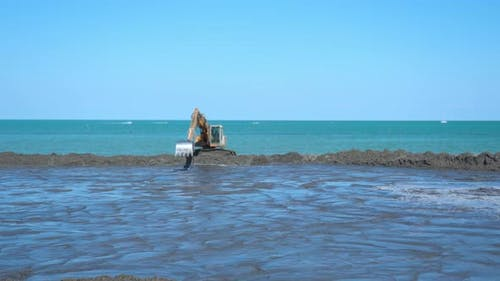 Timelapse of the Excavator Working in Front of the Sea