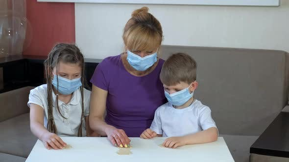 Mother and Children in Medical Masks Put Together Wooden Puzzles in the Room