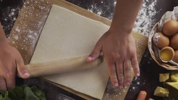 Thumbnail for Flat Lay Shot: Chef Rolls Out the Dough with a Rolling Pin on the Kitchen Table, Table Top