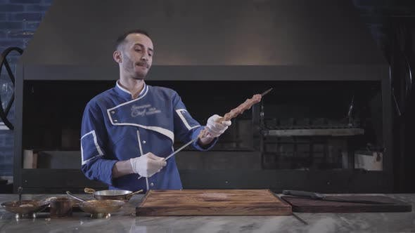 Cover Image for Skillful Man in Blue Chef Uniform Stringing Meat on a Skewer, Forming Lula Kebab in Modern