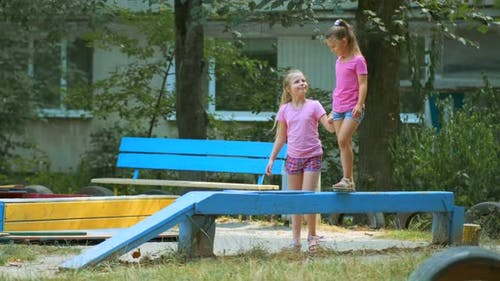 Two girls play in the Playground on a summer day. The elder sister helps the younger