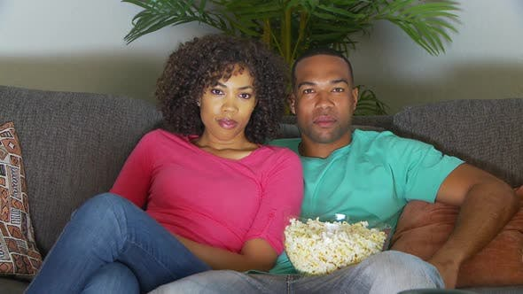 Thumbnail for Couple watching movie on couch while eating popcorn