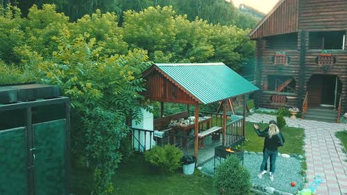 Aerial View: Young Guy with a Girl Is Making a Selfie, Near a Summer House, in the Mountains.