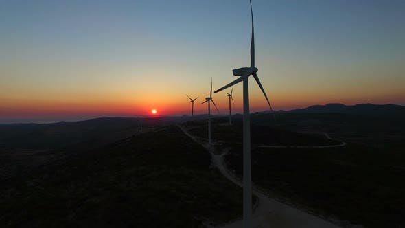 Thumbnail for Aerial view of windmills with slowly rotating blades at sunset