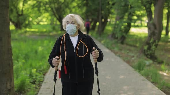 Thumbnail for Active Senior Old Woman in Mask Training Nordic Walking in Park at Quarantine