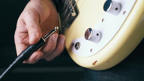 Person Connects Quarter-inch Amplifier Jack To Metal Output