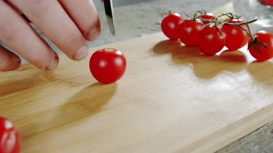 Cover Image for The Chef Cuts Tomatoes with a Knife on a Wooden Surface. Close Up