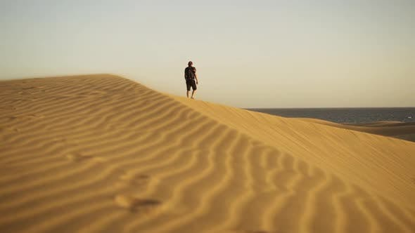 Thumbnail for Man Walking Along Top Of Rippled Sand Dune