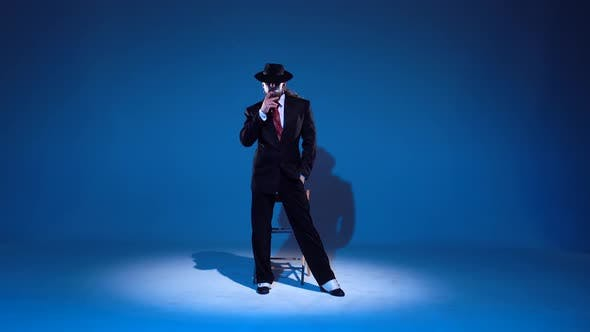 Thumbnail for Elegant Man in a Black Hat Is Dancing an Erotic Dance. Spotlight on a Blue Background.