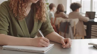 Woman Writing in Notebook in Classroom