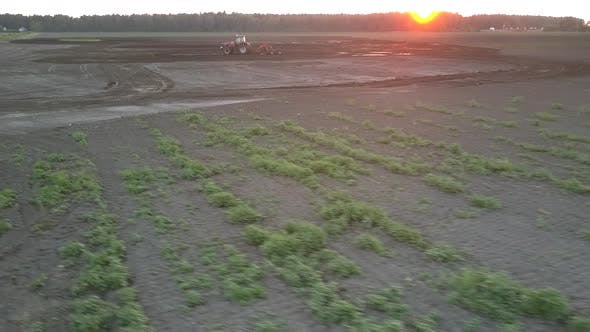Thumbnail for Wide Field and Cultivator Plowing Soil at Dusk Bird Eye View