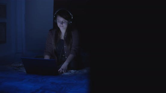 Woman with headphones on at night