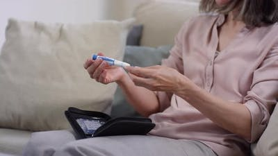 Woman Learning to Use Glucometer