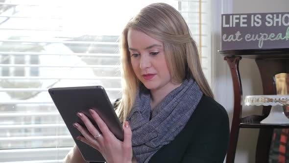 Thumbnail for A Young Blonde Female Inside Sitting And Swiping Her I Pad Tablet 1
