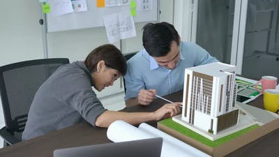 Business people working with building model
