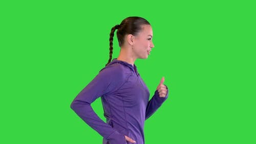 Female Runner in Sporty Outfit Jogging on a Green Screen Chroma Key