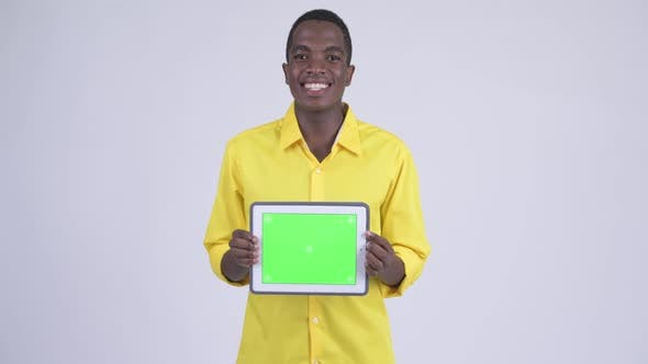 Thumbnail for Young Happy African Businessman Showing Digital Tablet and Looking Surprised