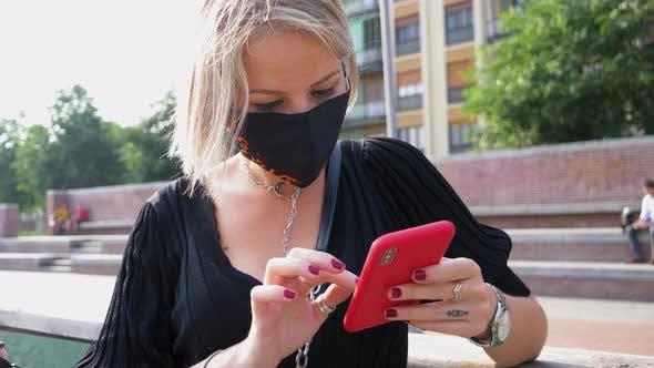 Woman wearing mask using smart phone