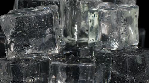 Pouring Soda Alcohol Vodka Tequila Gin Water Into Drinking Glass with Ice Cubes Slow Motion