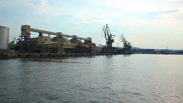 Thumbnail for Boat going by sea, approaching wharf with immense storehouses and cranes at port