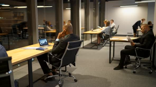 Businesspeople Talking Discussing and Using a Laptops, Tablets and Drawing at Office Desk Late at