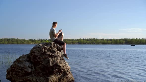 Thumbnail for A Young Man Sits on a Stone By the River with a Phone in His Hands. The Man Is Texting on His