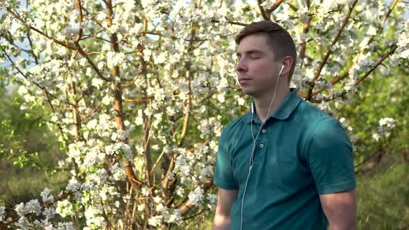 Young Man in Nature with Headphones in His Ears. A Man Listens To Music While Standing Against a