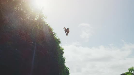 Thumbnail for Young man jumping and flipping off of huge tropical jungle cliff