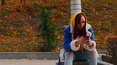 Young Woman with Mobile Phone in City Park